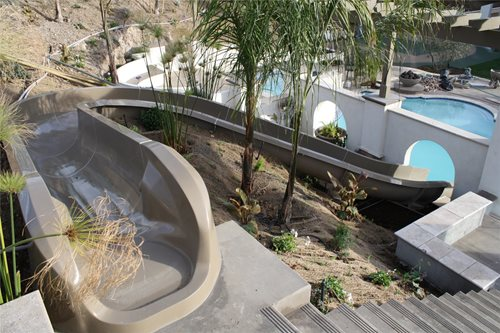 Backyard Hill Slide :  pool, rope swing, bocce court & more unite in a haciendastyle yard