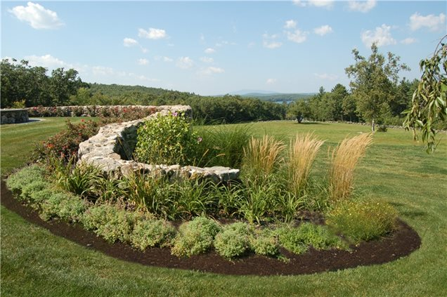 plants grow in planting beds on either side of a snaking stone wall
