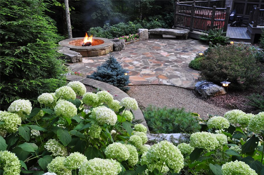 This is one of the best flagstone patio design ideas for sprucing up a  wooded area. The scene looks as if it is in a forest, with the woody  foliage and cozy ... - 21 Eye-Catching Flagstone Patio Design Ideas